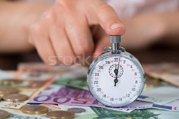 Person Hands With Stopwatch And Coins Over Banknote Stock photo © AndreyPopov