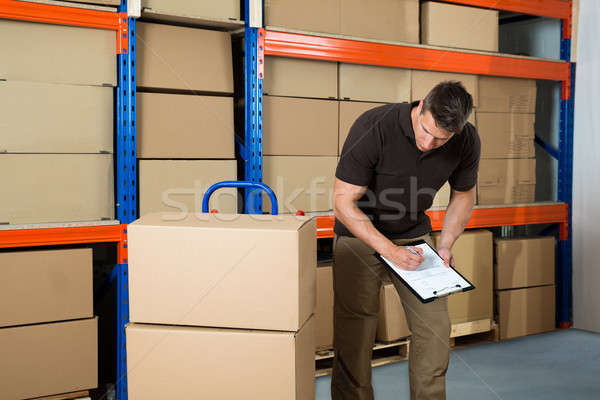Worker With Cardboard Boxes Writing On Clipboard Stock photo © AndreyPopov