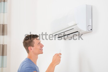 Man With Remote Control To Operate Air Conditioner Stock photo © AndreyPopov