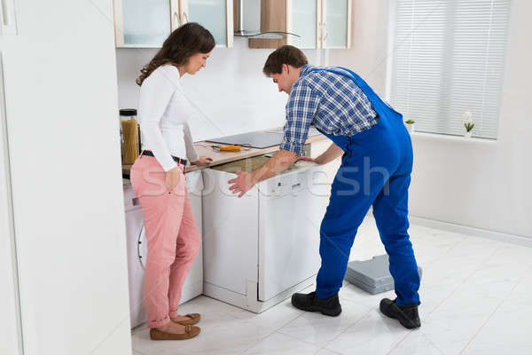 Worker Repairing Dishwasher While Woman In Kitchen Stock photo © AndreyPopov