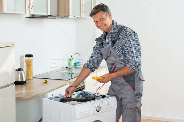 Stock photo: Technician Checking Washing Machine With Digital Multimeter