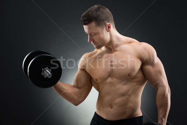 Determined Muscular Man Exercising With Dumbbells Stock photo © AndreyPopov