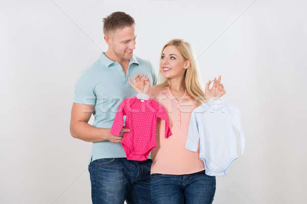 Couple Looking At Each Other While Holding Baby Clothing Stock photo © AndreyPopov