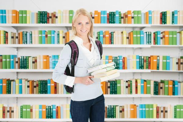 Női egyetemi hallgató áll könyvtár portré mosolyog Stock fotó © AndreyPopov