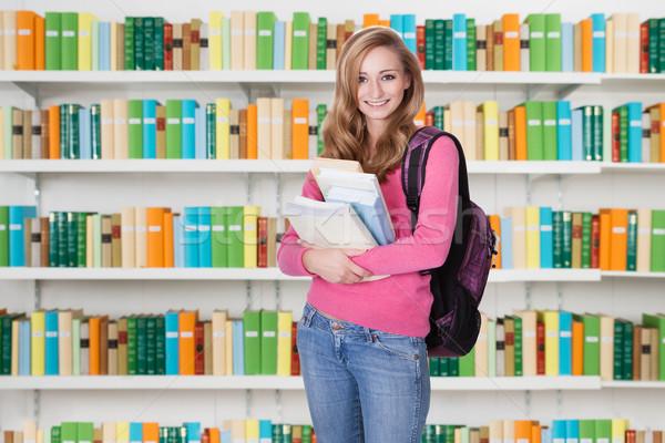 Gyönyörű egyetemi hallgató áll könyvtár portré női Stock fotó © AndreyPopov