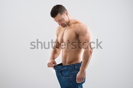 Muscular Man Looking At Weight Loss While Holding Old Jeans Stock photo © AndreyPopov