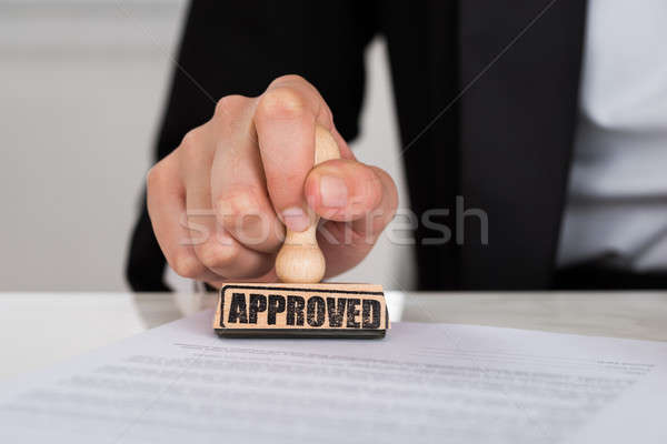 Businesswoman Stamping Approved On Contract Paper At Desk Stock photo © AndreyPopov