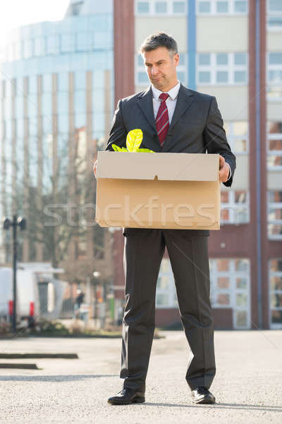 Businessman Standing With Cardboard Box Outside Office Stock photo © AndreyPopov