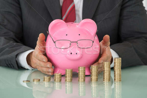Businessman Covering Piggy Bank With Stacked Coins At Desk Stock photo © AndreyPopov
