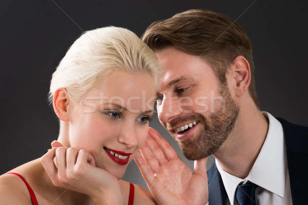Man Whispering In Woman's Ear Stock photo © AndreyPopov