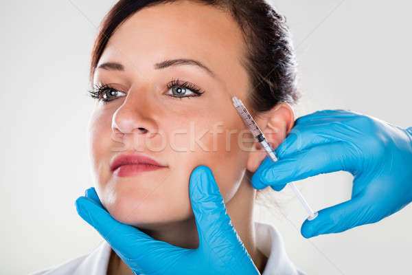 Person's Hand Injecting Syringe On Woman's Face Stock photo © AndreyPopov