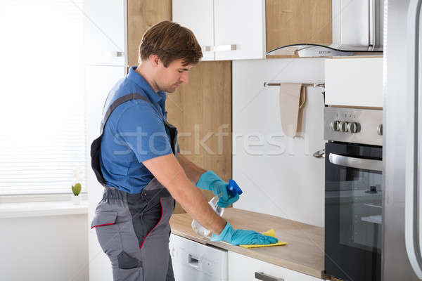Worker In Overall Cleaning Countertop Stock photo © AndreyPopov