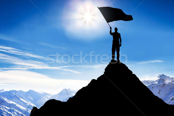 Silhouette Of A Man With Flag Standing On Mountain Peak Stock photo © AndreyPopov