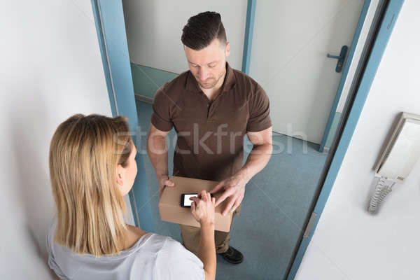 Young Woman Signing After Receiving Delivery Stock photo © AndreyPopov