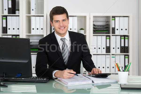 Young Accountant Working In Office Stock photo © AndreyPopov