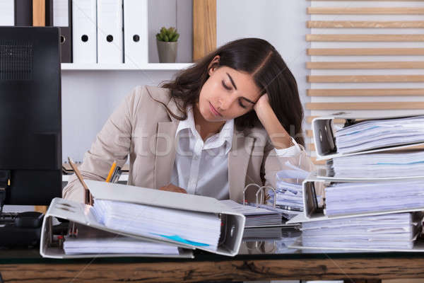 Businesswoman Working At Office With Stack Of Folders On Desk Stock photo © AndreyPopov