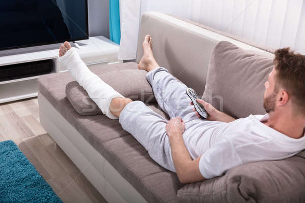 Man With Broken Leg Holding Remote Near Television Stock photo © AndreyPopov