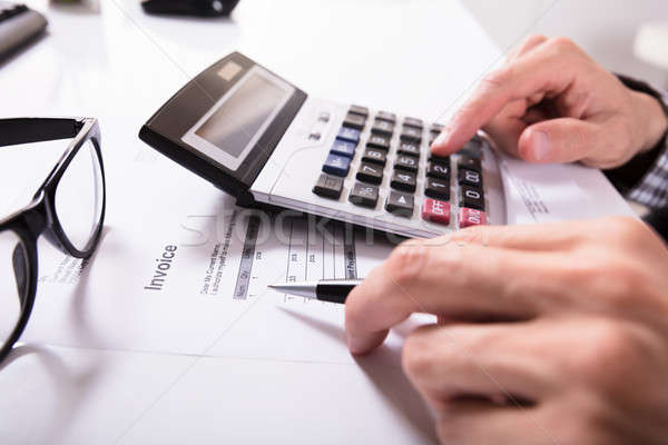 Businessman's Hands Calculating Invoice Stock photo © AndreyPopov