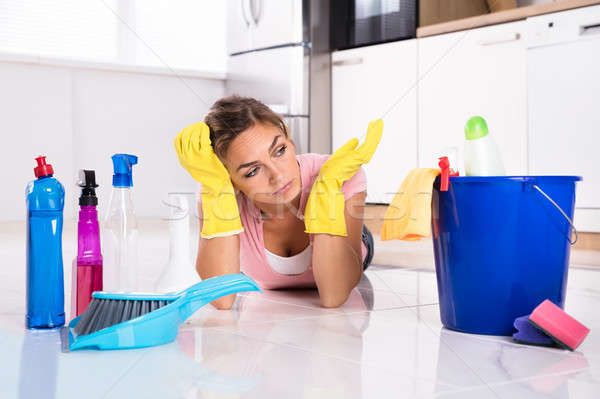 Woman Lying On Kitchen Floor And Looking At Cleaning Products Stock photo © AndreyPopov