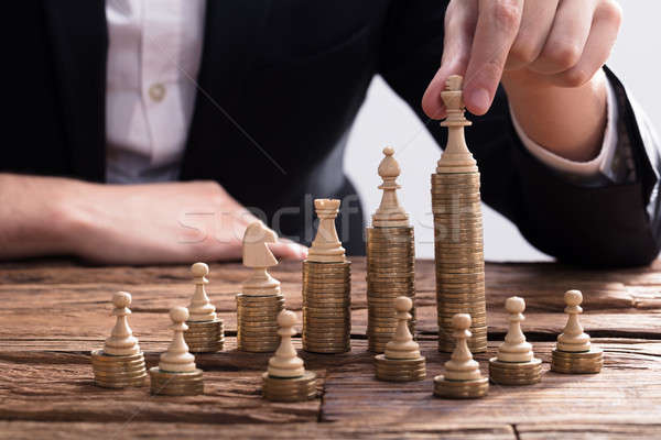 Businessperson Arranging Chess Piece On Stacked Coins Stock photo © AndreyPopov