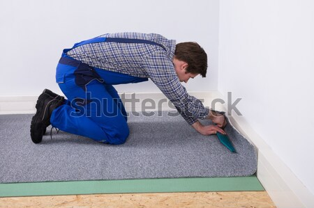 Worker Fitting Carpet On Floor Stock photo © AndreyPopov