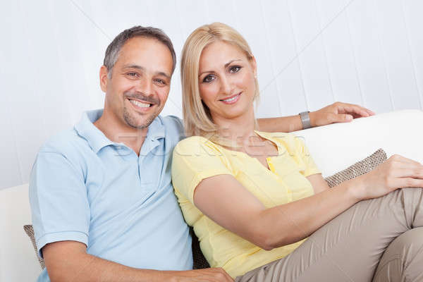 Loving couple relaxing on a sofa Stock photo © AndreyPopov