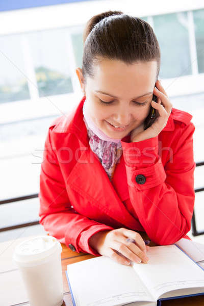 Happy woman looking at diary and talking on cell phone Stock photo © AndreyPopov