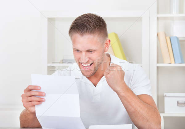 Man cheering in jubilation as he reads a letter Stock photo © AndreyPopov