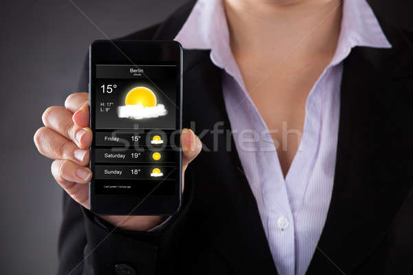 Businessperson Showing Weather Forecast On Mobile Phone Stock photo © AndreyPopov