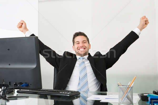 Successful Businessman With Arms Raised At Desk Stock photo © AndreyPopov