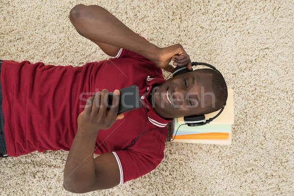 Man Lying On Stack Of Books Listening Music On Headphones Stock photo © AndreyPopov