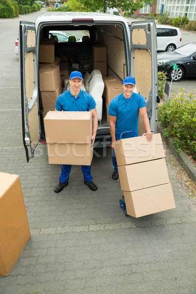 Stock photo: Two Workers Loading Cardboard Boxes In Truck