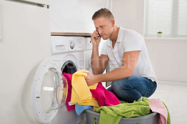Uomo cestino di lavanderia cellulare giovane parlando lavanderia Foto d'archivio © AndreyPopov