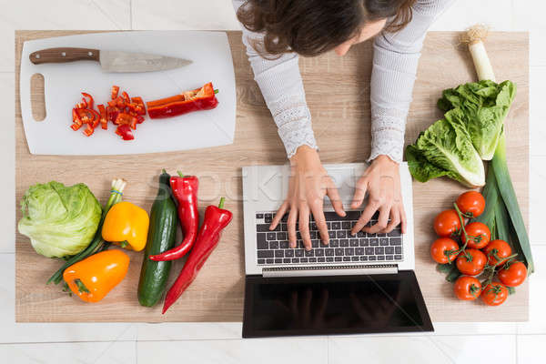 Woman Using Laptop In Kitchen Stock photo © AndreyPopov