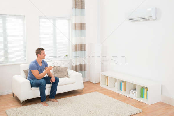 Young Man Operating Air Conditioner Stock photo © AndreyPopov