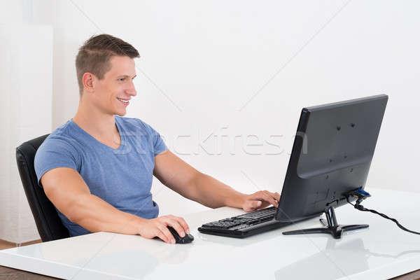 homme travail ordinateur de bureau jeune homme bureau heureux photo stock. Black Bedroom Furniture Sets. Home Design Ideas