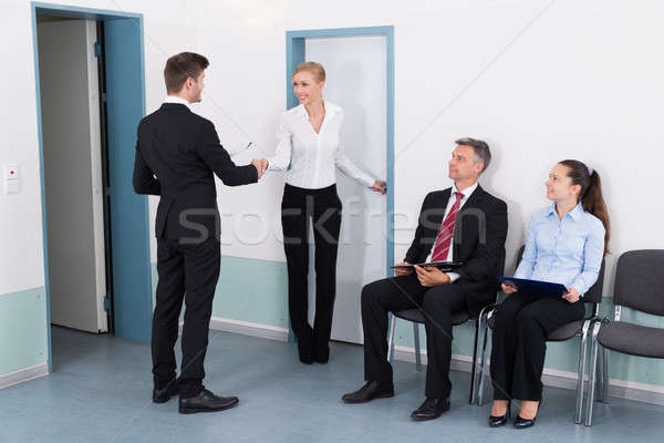 Businesswoman Shaking Hands With Man In Front Of People Stock photo © AndreyPopov