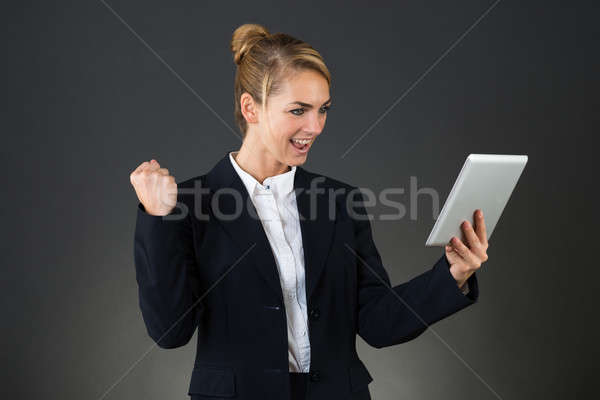Businesswoman Celebrating Victory While Using Digital Tablet Stock photo © AndreyPopov