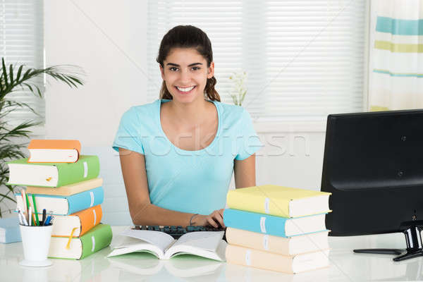 Female Student Using Computer While Studying At Table Stock photo © AndreyPopov