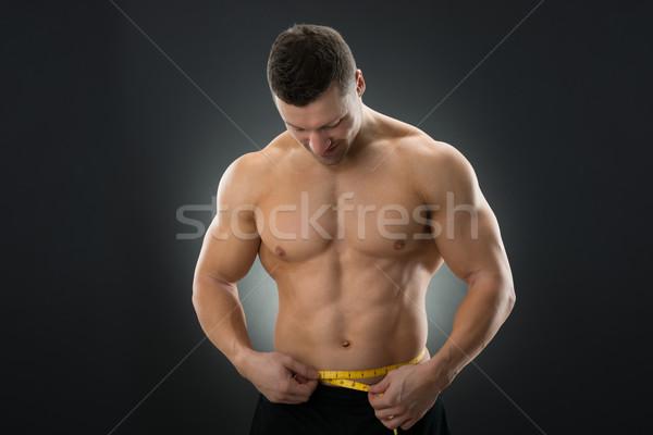 Muscular homem fita métrica preto Foto stock © AndreyPopov