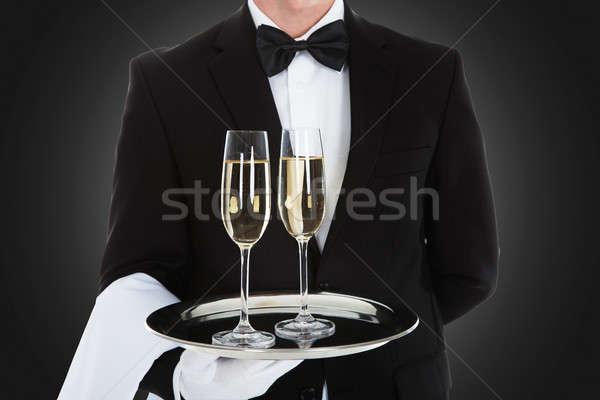 Pincér hordoz pezsgő fuvolák tálca szürke Stock fotó © AndreyPopov