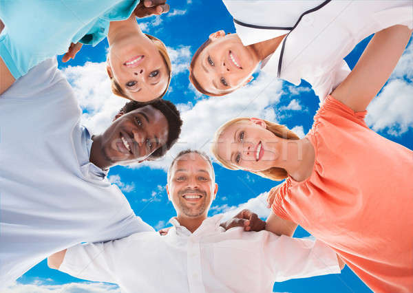Happy Multiethnic Friends Forming Huddle Against Sky Stock photo © AndreyPopov