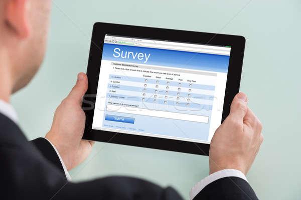 бизнесмен глядя онлайн обзор форме цифровой Сток-фото © AndreyPopov