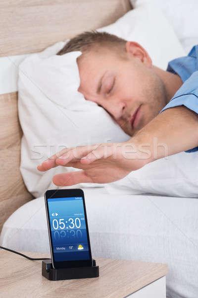 Man Snoozing Alarm On Mobile Phone Screen Stock photo © AndreyPopov