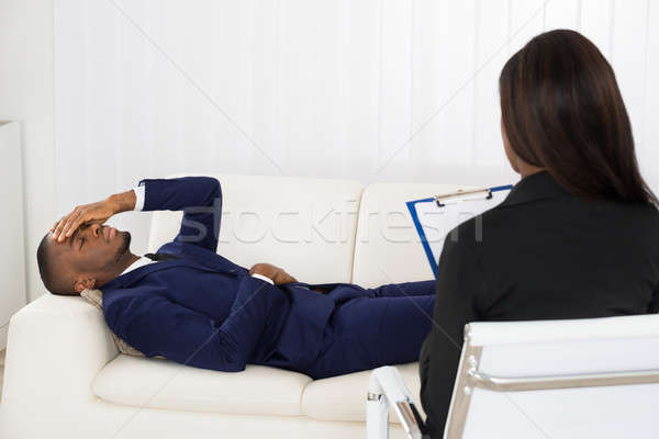 Stock photo: Patient Laying On Couch In Front Of Psychiatrist