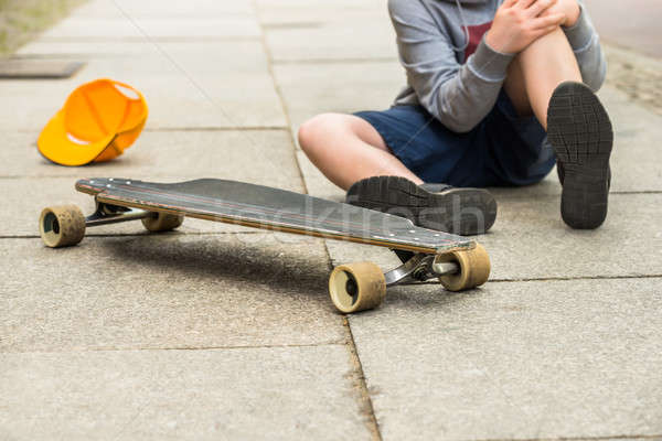 Boy With Knee Injury Sitting On Sidewalk Stock photo © AndreyPopov
