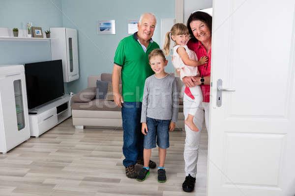 Büyükbaba veya büyükanne torunlar ayakta arkasında kapı mutlu aile Stok fotoğraf © AndreyPopov