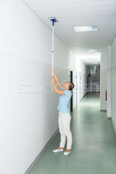 Woman Cleaning The Ceiling With Mop Stock photo © AndreyPopov