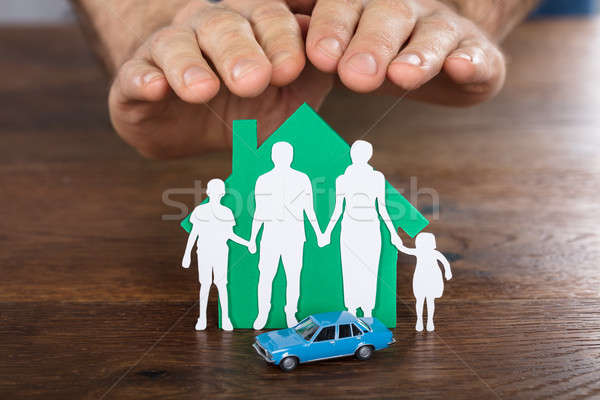 Person Protecting House Model With Family On It Stock photo © AndreyPopov