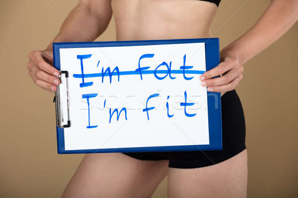 Woman Holding Clipboard With I'm Fat And I'm Fit Text Stock photo © AndreyPopov